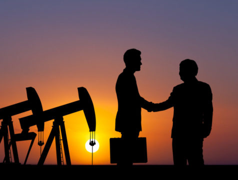 the-silutet-of-two-people-shaking-hands-with-oil-pumps-in-the-background-1.jpg