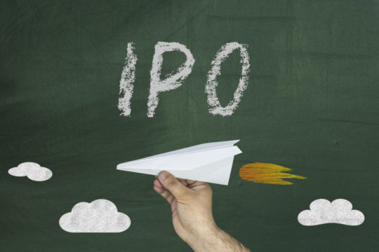 a-person-holding-a-paper-airplane-with-a-chalk-board-in-the-background-containing-the-word-ipo-1.jpg
