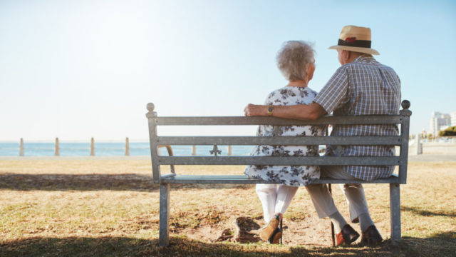 elderly-senior-couple-sitting-on-a-bench-on-the-beach-1.jpg