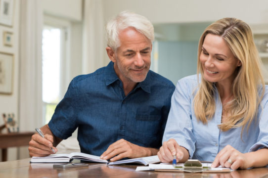 mature-couple-discussing-finances-with-pens-and-paper-1.jpg